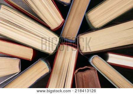 Stack of hardback books background. Many colorful books piles, close-up. Education concept