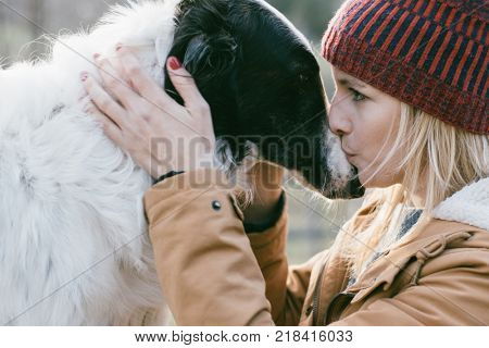 Beautiful woman kissing her dog outdoors. Girl with her dog. Cute dog loves her owner.