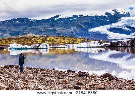 The elderly woman photographs the lagoon. The concept of extreme northern tourism. Ice floes are reflected in the smooth water surface of Ice Lagoon Jokulsarlon, Iceland