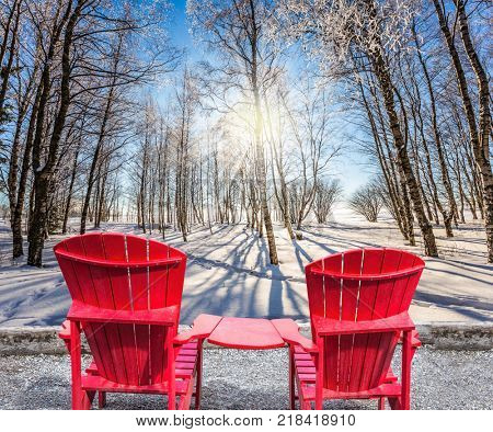 Bright winter frosty day. Comfortable red plastic chaise lounges for relaxing. Sunset in the Arctic. The concept of extreme and ecotourism tourism