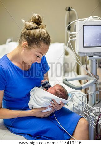 Mother holding her newborn premature baby in the hospital