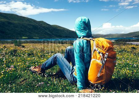 young backpacking woman sit on flowers and grass in high altitude mountains