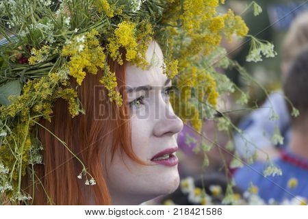 Ukraine, Kiev, Park Pirogovo. Celebration of the pagan festival of Ivan Kupala. July 7, 2017: A beautiful woman in a wreath of wildflowers.