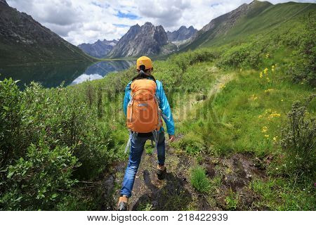 young backpacking woman walking in high altitude mountains