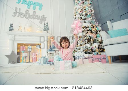Emotional little girl. Happy New Year. Pleasure, happiness and delight from New Year's gifts