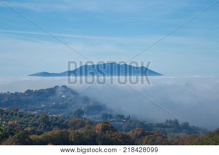 Sabina hills immersed in the fog with the Monte Soratte in the background.
