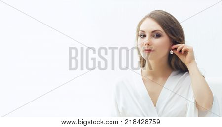 Beauty portrait of attractive and young woman trying pearl earrings.