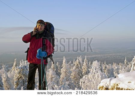 smiling traveler man at the top of a mountain talking on a mobile phone in the background of a winter landscape