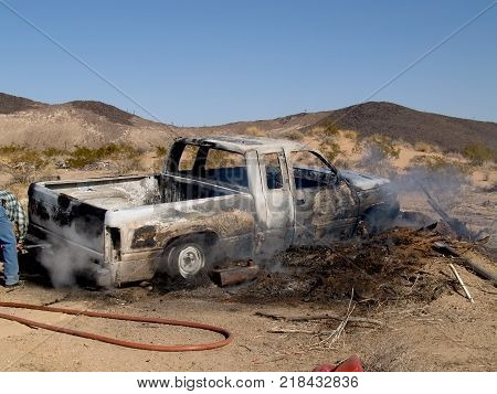 Taken in 2007. A stolen pickup truck that was burned in the Arizona desert. The man on the far left is a volunteer firefighter. No model release is necessary.