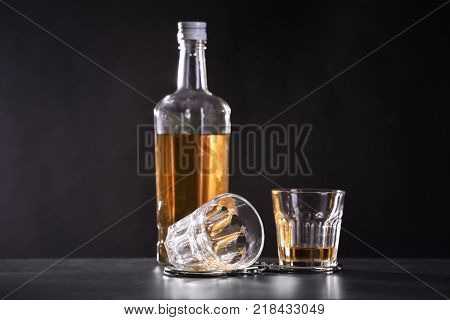 Bottle and glasses with handcuffs on dark background. Alcohol dependence concept