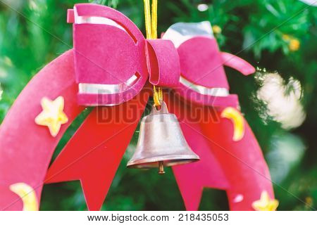 Christmas decoration, red ribbon and jingle bell on pine tree branch