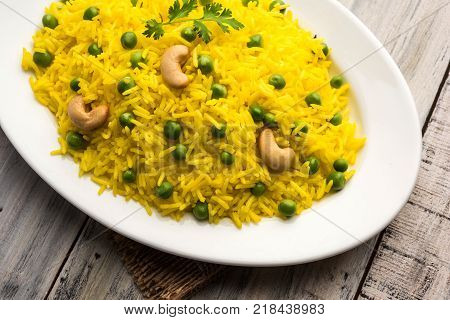 Basmati Rice Pilaf or pulav with Peas, or vegetable rice using green peas also known as matar pulav, with added yellow colour, served with plain dal