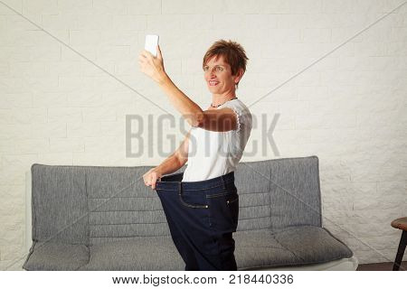 Senior woman taking selfie, showing her weight loss