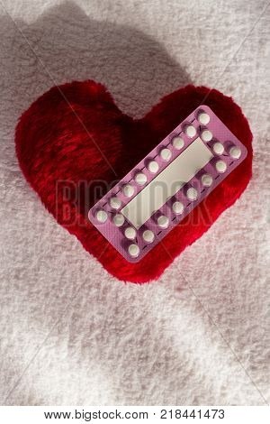 Medicine contraception love and birth control. Oral contraceptive pills on red heart shaped little pillow