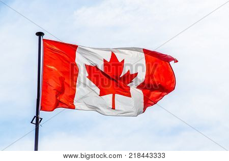 Canadian flag flying against the blue sky.