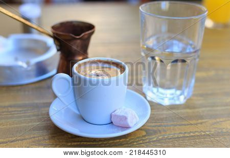 Turkish coffee served with a coffee pot on a wooden table