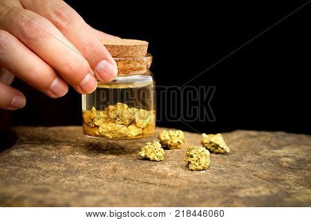 Human hands are holding bottles that contain pure gold minerals found in mines on black background with copy space for your text