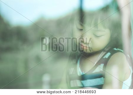 Asian child girl are standing by the mirror reflecting in a lonely mood depressed and anxious