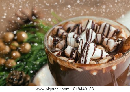 Hot chocolate in cup topping with marshmallow and chocolate sauce. Delicious hot chocolate or cacoa on wood table in close up view, copy space with Christmas theme and snowfall background. Concept to present Xmas drink. Homemade hot chocolate.