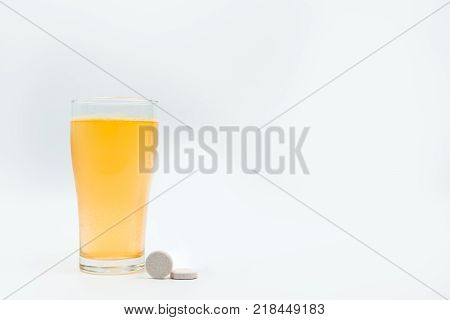Two effervescent tables on white background and orange effervescent bubbles of calcium and vitamin C effervescent tablets in transparent glass. Vitamins minerals and supplement concept.