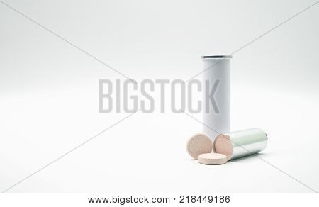 Effervescent tables tube with blank label and copy space on white background. Calcium and vitamin C effervescent tablets are removed from the foil packaging. Vitamins minerals and supplement concept.