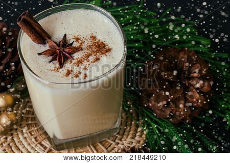 Eggnog traditional drink for Christmas celebration party. Homemade eggnog in glass topped with ground nutmeg and cinnamon stick in top view with copy space. Delicious eggnog in Xmas theme decoration and snowfall effect background. Eggnog ready to served.