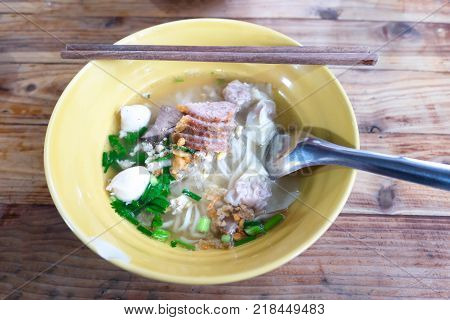 Close up Pork Hot Noodles with Dumpling Thai Style in Yellow Ceramic Bowl on Wood Table