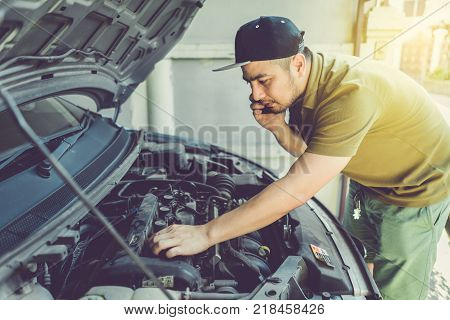 Mechanic technician man holding clipboard and check the car engine looking at chart note. car service repair fixing checking maintenance working at workshop. inspection vehicle concept.