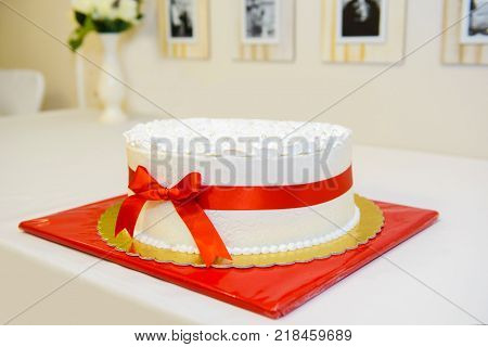 Birthday cake with red bow. Bows on anniversary cakes. Delicious sweet symbolic cooking the festive feast. poster