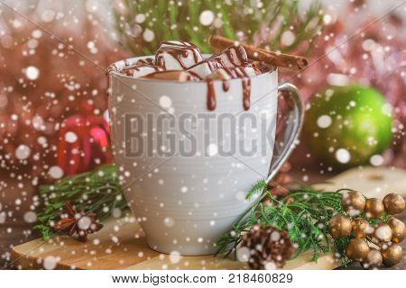 Hot chocolate in white cup topping with marshmallow and dark chocolate sauce. Homemade hot cacao or chocolate on wood table in side view copy space with Christmas theme and snowfall bokeh background.Delicious eggnog in concept to present Christmas drink.