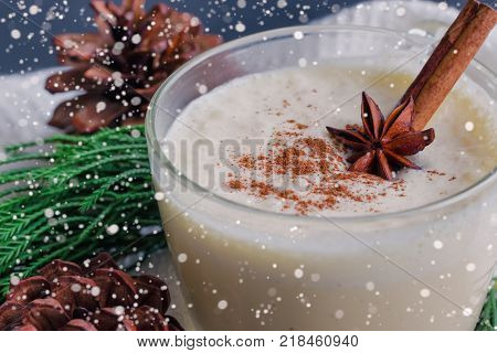 Eggnog traditional drink for Christmas celebration party. Homemade eggnog in cup topped with ground nutmeg and cinnamon stick. Close up eggnog with copy space in Christmas theme decoration and snowfall effect background. Delicious eggnog ready to served.
