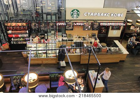 ST. PETERSBURG, RUSSIA - DECEMBER 9, 2017: Starbucks Coffee Shop Interior in Shopping Mall Food Hall. Shop-window Counter with Barista and Sitting Area with Tables and Customers Top View.