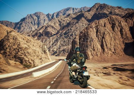 Motorcyclist rushes along the picturesque desert mountain highway. sport bike