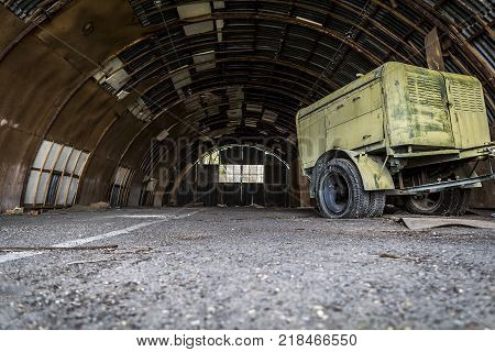 ever used hangar now abandoned and half-destroyed and one non-working aggregate in it. dark, dirty and broken hangar.