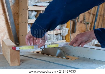 Carpenter taking measurments at the table saw in a small workshop