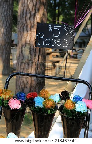Vertical image with black buckets that hold handcrafted glass roses with small chalkboard advertising them for five dollars.