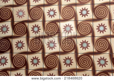 Horizontal background image with colorful swirls and diamond shape designs in the colors of brown, tan and blue.
