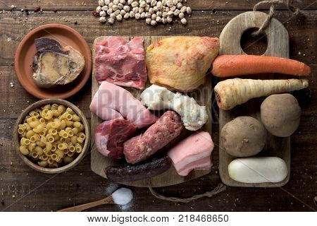 high angle shot of the raw vegetables and meat to prepare escudella, a soup typical of Catalonia, Spain, such as carrot, potato, chickpeas or turnip, and different pieces of chicken, beef and pork
