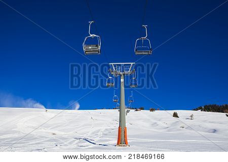 Chairlift without people. The cable car on the blue sky in the Dolomites. Cableway in the mountains without people. Artificial snowing ski by Snow cannon maker. Alpe di Siusi Italy in winter.