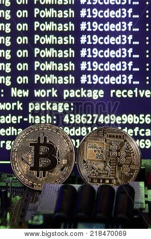 Two bitcoins lies on a videocard surface with background of screen display of cryptocurrency mining by using the GPUs