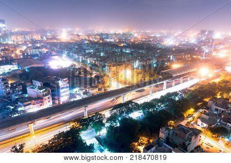 aerial view of the cityscape of Noida gurgoan delhi at night  with the elevated metro track and metro station visible. The city residences and offices are also clearly visible