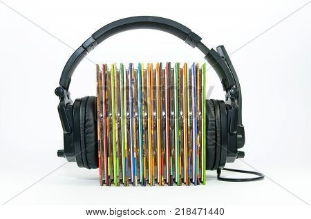 Black headphone , stack of colorful music cd, isolated on white background, love of music conceptual image.