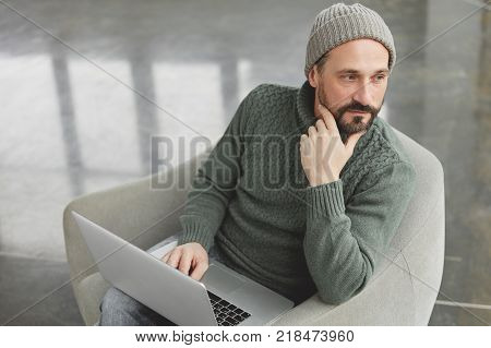 Portrait Of Pensive Bearded Middle Aged Male Writer Wears Knitted Sweater And Hat, Sits In Comfortab