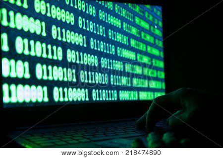 Credit card thief , credit card on laptop keyboard, binary number system on the laptop screen. Conceptual image of internet security, fraud.