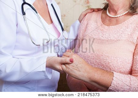 Female Patient Being Reassured By Doctor at home Room