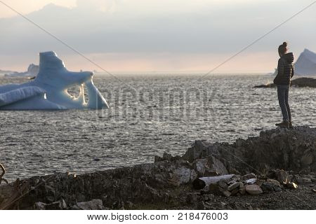 woman standing on rocks watching Newfoundland icebergs on Fogo Island