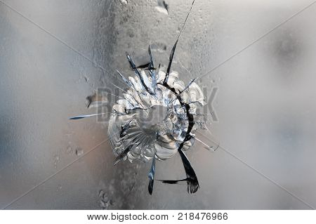 Broken glass. Hole cracks in the window from the fragment of the projectile. Avdeevka. Ukraine. Background texture