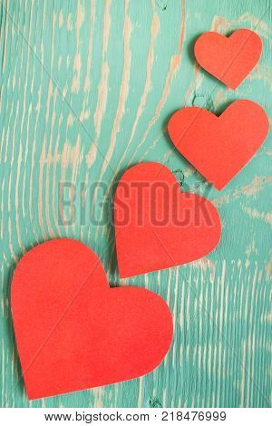 Wavy line of red paper hearts on light green painted textured with squiggly stripes wooden table. Top view.