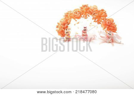 High angle view of three  cute little baby dolls  with brown  hair wearing diaper with pacifier in mounth sitting on cloth flower with blue ribbon. close-up shot. with copy space isolated on white background