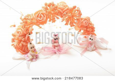 High angle view of three  cute little baby doll  with brown  hair wearing diaper with pacifier in mounth sitting on cloth flower with blue ribbon. close-up shot. with copy space isolated on white background
